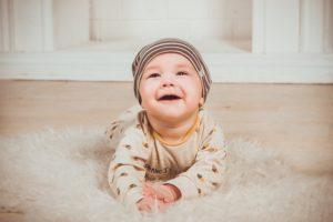寝転がりながら笑う赤ちゃん