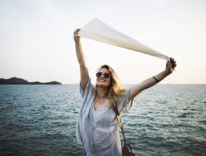 海で両手をあげる女性
