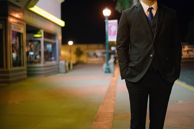 夜道を歩くスーツ姿の男性