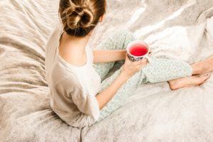 ベッドの上で紅茶を飲む女性