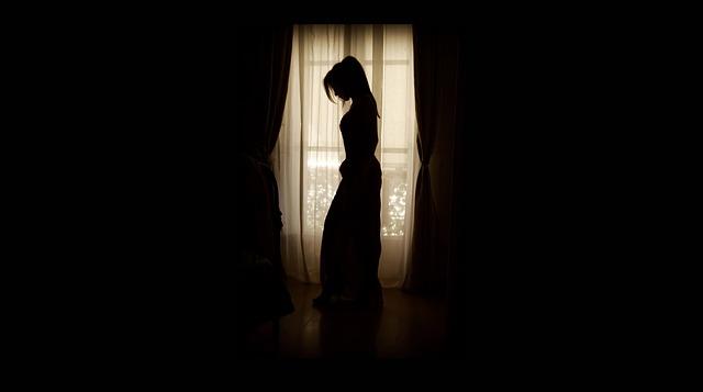 暗い部屋でうつむく女性