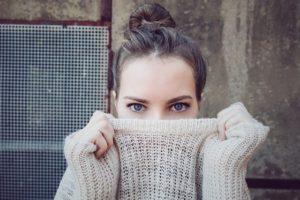 セーターで顔を隠す女性