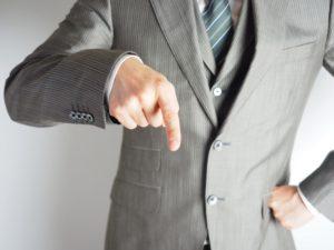 指をさして注意をしているスーツ姿の男性
