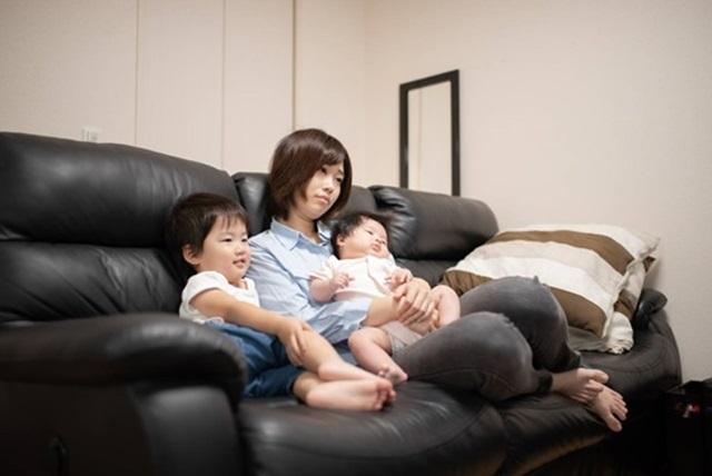 ソファに座りながら幼い子供をあやす母親