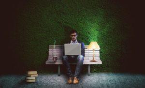 暗い公園でパソコンを打つ男性