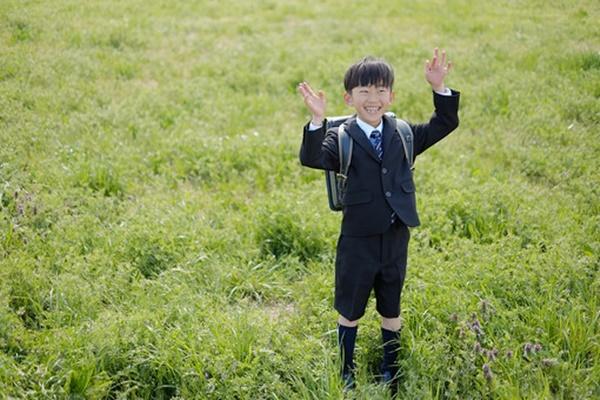 原っぱで笑顔の小学生の男の子