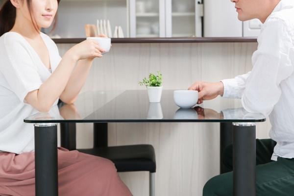テーブルでお茶を飲みながら相談事をする夫婦