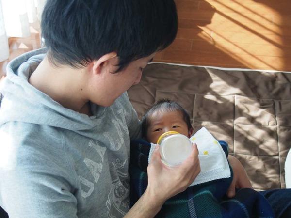 赤ちゃんにミルクをあげるお父さん